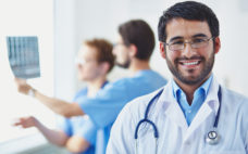 Portrait of smiling doctor looking at camera on background of his working colleagues