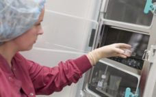 Embryologist putting sample into incubator (selective focus)