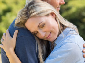 Close up face of senior woman with eyes closed hugging her husband. Romantic mature couple in love embracing outdoors. Satisfied senior wife hugging husband and feeling good.