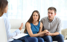 Worried couple listening to marriage counselor during a therapy sitting on a sofa at home