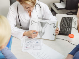 Concentrated doctor is sitting at table. She showing and explaining functioning of reproductive system of woman