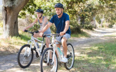 Active senior couple riding bikes during vacation. Happy mature couple cycling through the park. Retired man and smiling mature woman cycling with mountain bike.