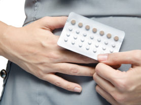 Woman holding contraceptive pills rotect for pregnant