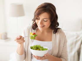 healthy eating, dieting and people concept - smiling young woman eating vegetable salad at home