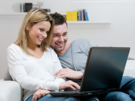 Young couple relaxing on the couch with laptop in their living room at home